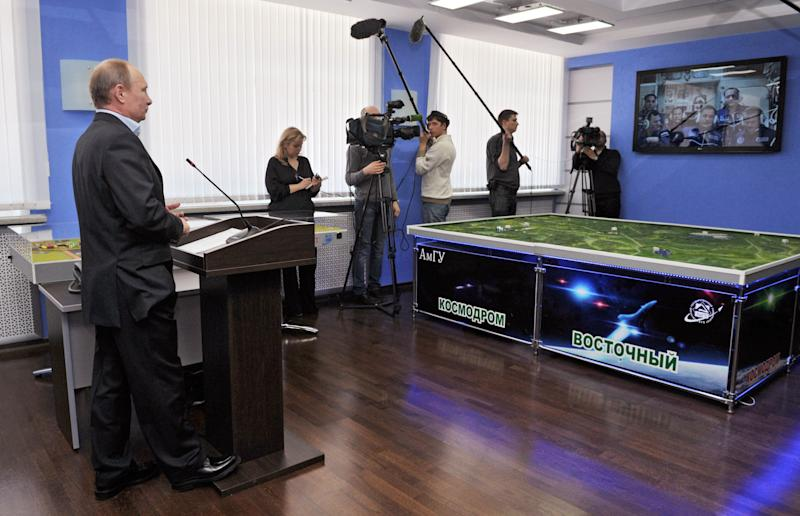 Russian President Vladimir Putin, left, listens during a live video link with the International Space Station from a construction site of new cosmodrome Vostochny ( Eastern) at Eastern Siberia on Friday, April 12, 2013. Russia celebrates 52nd anniversary of the first manned space flight on April 12. Cosmodrome Vostochny is written in Cyrillic in the middle. Putin said on Friday Russia would continue to lease the Baikonur space complex in Kazakhstan despite recent statements from space officials that Russia may suspend its lease. (AP Photo/RIA Novosti, Alexei Nikolsky, Presidential Press Service, Pool)