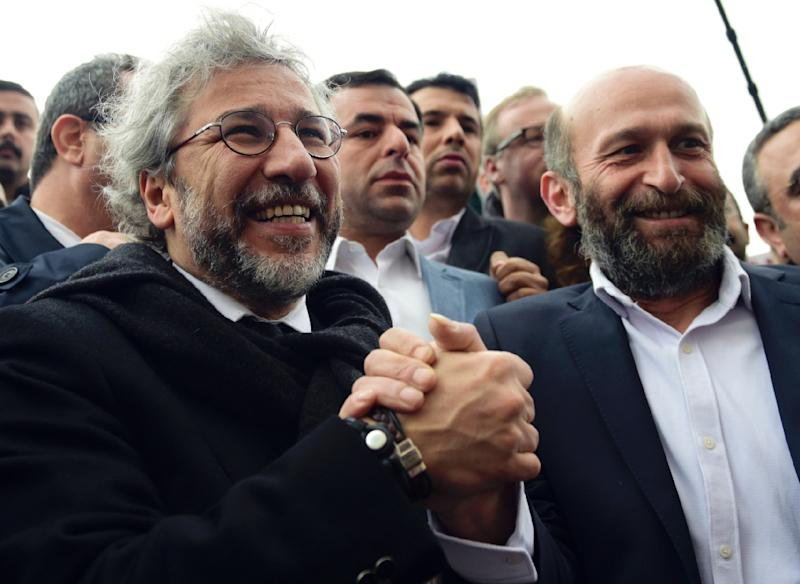 Editor-in-chief of Turkish daily Cumhuriyet, Can Dundar (L), and Ankara editor Erdem Gul hold hands as they arrive at the Istanbul courthouse before their trial on March 25, 2016 (AFP Photo/Bulent Kilic)