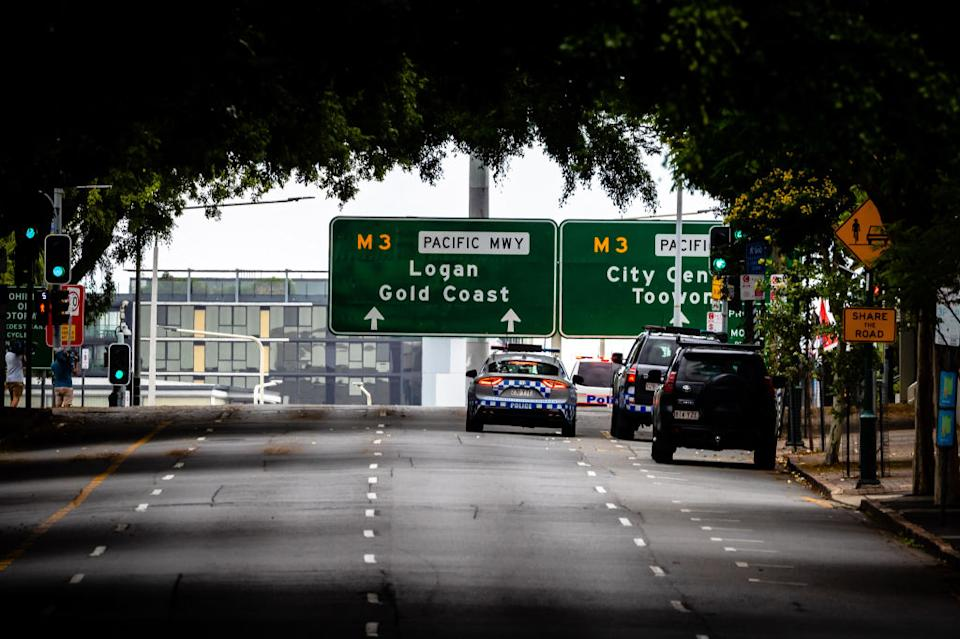 Police vehicles are seen on a deserted street on the first day of a snap lockdown in Brisbane.