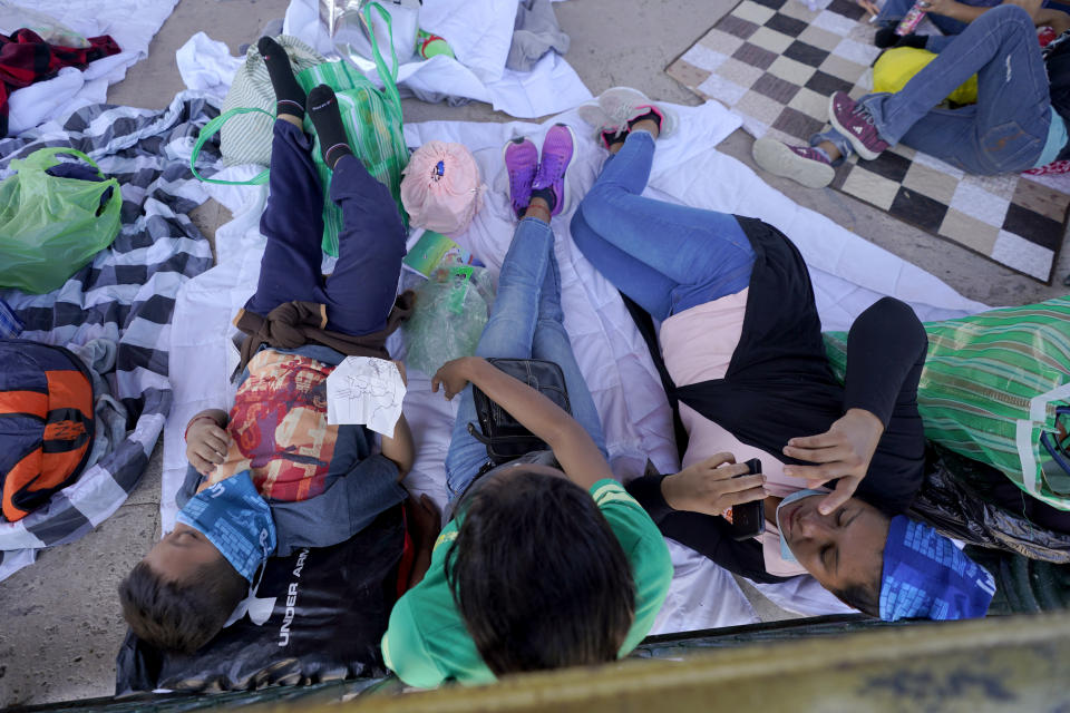 Migrants rest in a gazebo at a park after a large group of deportees were pushed by Mexican authorities off an area they had been staying after their expulsion from the U.S., Saturday, March 20, 2021, in Reynosa, Mexico. A surge of migrants on the Southwest border has the Biden administration on the defensive. The head of Homeland Security acknowledged the severity of the problem Tuesday but insisted it's under control and said he won't revive a Trump-era practice of immediately expelling teens and children. An official says U.S. authorities encountered nearly double the number children traveling alone across the Mexican border in one day this week than on an average day last month. (AP Photo/Julio Cortez)