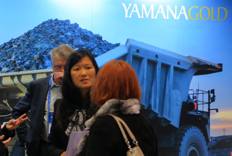 FILE PHOTO: Visitors to the Yamana Gold mining company booth speak with representatives during the PDAC convention in Toronto