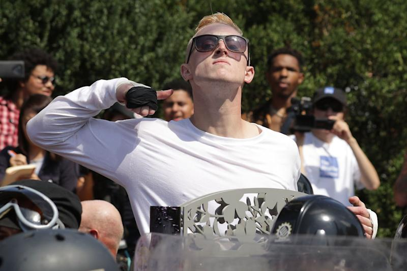 "A man makes a slashing motion across his throat toward counter-protesters as he marches with other white nationalists and neo-Nazis during the ""Unite the Right"" rally."