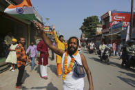 A Hindu devotee waves an Indian national flag and celebrates a verdict in a decades-old land title dispute between Muslims and Hindus, in Ayodhya, India , Saturday, Nov. 9, 2019. India's Supreme Court on Saturday ruled in favor of a Hindu temple on a disputed religious ground and ordered that alternative land be given to Muslims to build a mosque. The dispute over land ownership has been one of the country's most contentious issues. (AP Photo/Rajesh Kumar Singh)