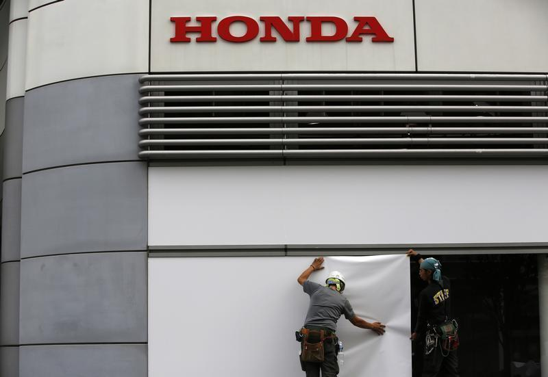 Workers stand under the logo of Honda Motor Co. outside the company's headquarters in Tokyo