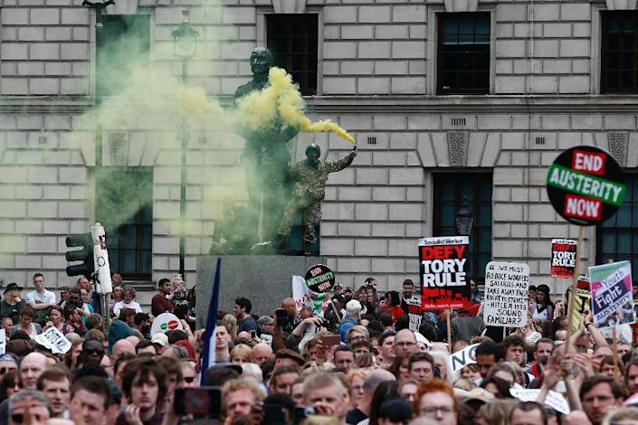 A demonstrator stands on the statue of former South African prime minister Jan Smuts in Parliament Square holding a smoke flare as thousands gather to listen to anti-austerity speechesin London on June 20, 2015 (AFP Photo/Justin Tallis)