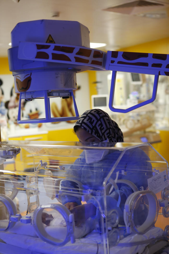A nurse takes care of one of the nine babies protected in an incubator at the maternity unit of the Ain Borja clinic in Casablanca, Morocco, Thursday May 20, 2021, two weeks after Mali's Halima Cisse, 25, gave birth to nine healthy babies. (AP Photo / Abdeljalil Bounhar)