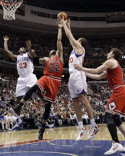 Chicago Bulls' Taj Gibson (22) goes up for a rebound between Philadelphia 76ers' Spencer Hawes (00) and Lou Williams (23) as Omer Asik (3), of Turkey, pushes in during the first half of Game 6 in an NBA basketball first-round playoff series on Thursday, May 10, 2012, in Philadelphia. (AP Photo/Matt Slocum)