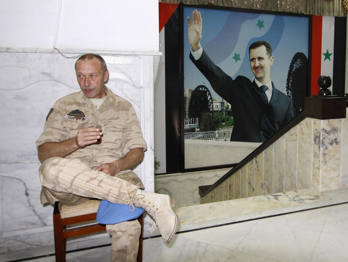 In this picture taken during a UN observer-organized media tour, a UN observer drinks tea as he sits next to a poster of Syrian President Bashar Assad at the governorate building in Hama city, central Syria, on Thursday May 3, 2012. Syrian security forces stormed dorms at a northwestern university to break up anti-government protests there, killing at least four students and wounding several others with tear gas and live ammunition, activists and opposition groups said Thursday. (AP Photo/Muzaffar Salman)