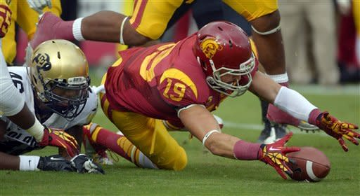 Southern California safety Drew McAllister recovers a fumble by Colorado fullback Christian Powell, left, during the first half of an NCAA college football game, Saturday, Oct.20, 2012, in Los Angeles. (AP Photo/Mark J. Terrill)