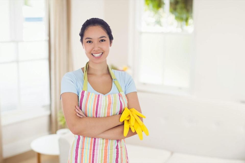 Woman holding gloves and wearing an apron against sitting room