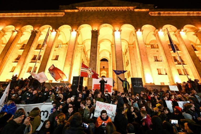 Protesters demanding the government's resignation and early parliamentary polls rally in front of the parliament in Tbilisi