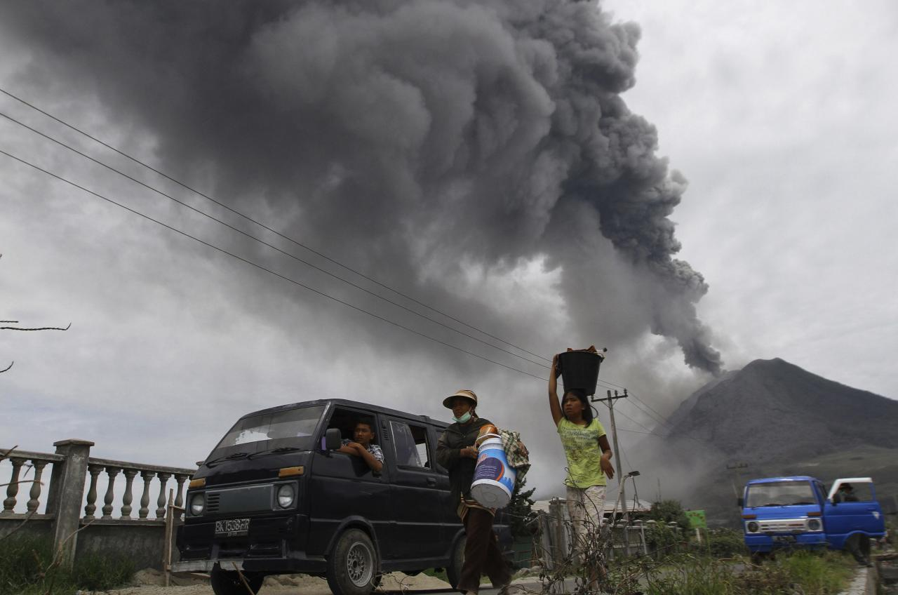 Villagers move to safety as Mount Sinabung spews ash and hot lava during an eruption in Perteguhan village in Karo district, Indonesia's north Sumatra province, September 17, 2013. Mount Sinabung threw more volcanic ash into air, covering the surrounding areas on Tuesday, as authorities prepared more temporary shelters for evacuees. REUTERS/Roni Bintang (INDONESIA - Tags: DISASTER ENVIRONMENT)