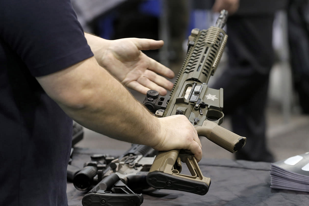 A vendor shows rifles at the Border Security Expo in Phoenix.