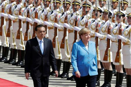 German Chancellor Angela Merkel and Chinese Premier Li Keqiang review the guard of honour during a welcome ceremony outside the Great Hall of the People in Beijing, China May 24, 2018. REUTERS/Jason Lee