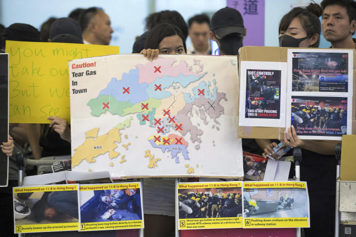 Protesters show posters to travelers at the arrival hall of the Hong Kong International Airport in Hong Kong, Tuesday, Aug. 13, 2019. (Photo: Vincent Thian/AP)