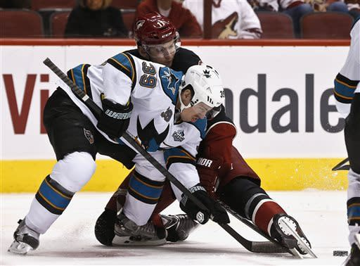 San Jose Sharks' Logan Couture (39) battles Phoenix Coyotes' Martin Hanzal (11), of the Czech Republic, for the puck after a face off in the first period during an NHL hockey game, on Monday, April 15, 2013 in Glendale, Ariz. (AP Photo/Ross D. Franklin)