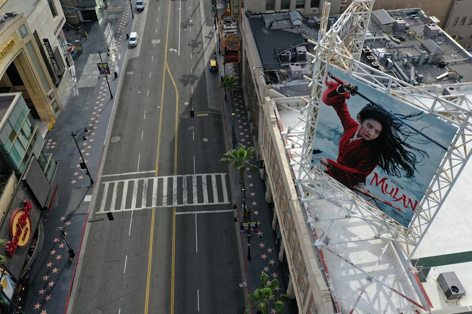 """A poster of the Walt Disney Studios' """"Mulan"""" movie, which was going to be released on March 27, towers over an empty Hollywood Boulevard during the global outbreak of coronavirus disease (COVID-19), in Hollywood, Los Angeles, California, U.S., March 31, 2020.  REUTERS/Lucy Nicholson"""