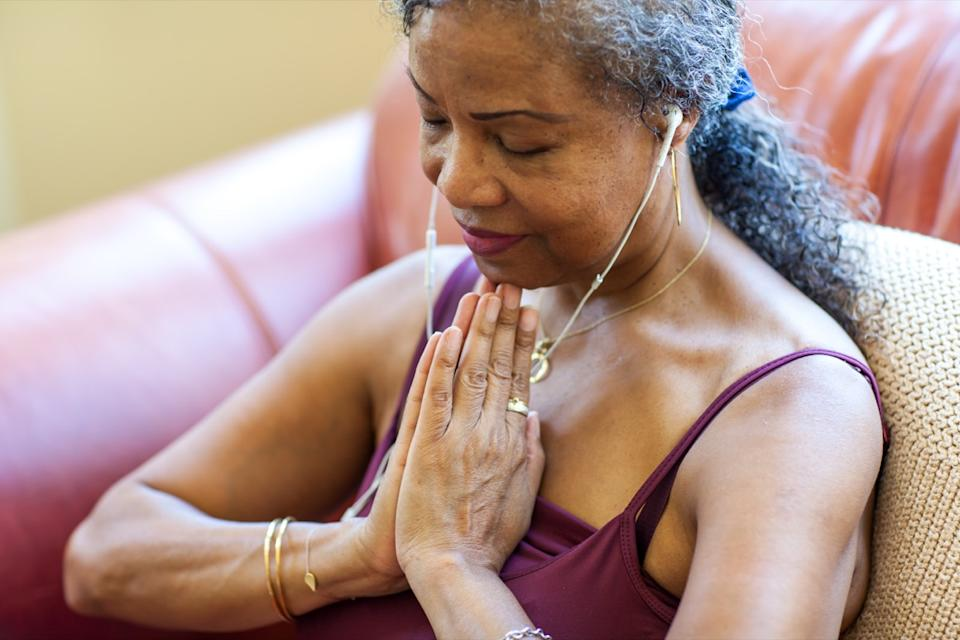 Older woman listening to music and meditating on the couch