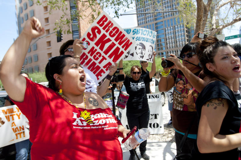 Jovana Renteria, of Phoenix, left, protests against Maricopa County Sheriff Joe Arpaio in front of the U.S. District Courthouse in Phoenix on Tuesday, July 24, 2012. Arpaio was on the witness stand today for a federal racial profiling lawsuit involving his office. (AP Photo/The Arizona Republic, David Wallace) MARICOPA COUNTY OUT; MAGS OUT; NO SALES