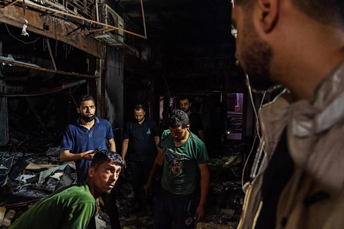 Shopkeepers try to salvage what they can from their damaged stores.