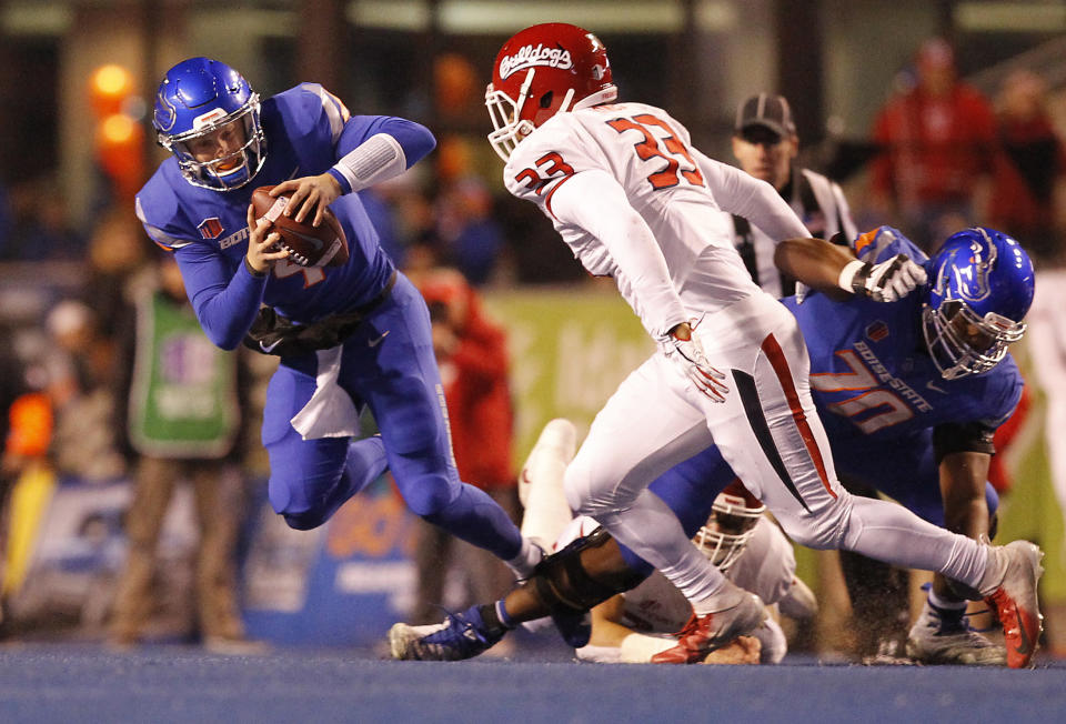 Boise State quarterback Brett Rypien (4) is tripped up by a Fresno State play for a loss during an NCAA college football game Friday, Nov. 9, 2018, in Boise, Idaho. (Drew Nash/The Times-News via AP)