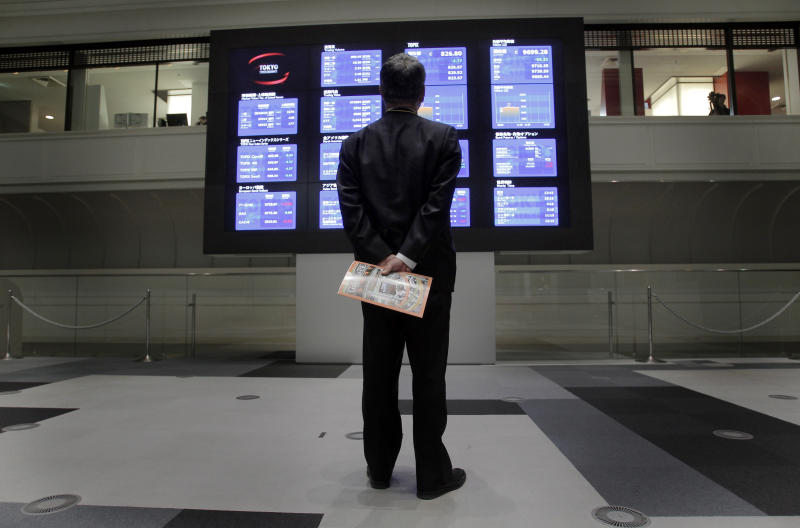 A man looks at the electronic stock price board at the Tokyo Stock Exchange in Tokyo, Friday, April 6, 2012. Asian stock markets were muted Friday in holiday-thinned trade ahead of a monthly U.S. hiring report. (AP Photo/Itsuo Inouye)
