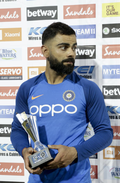 "India captain Virat Kohli holds the ""Man of the Match"" trophy at the end of the third One-Day International cricket match against West Indies in Port of Spain, Trinidad, Wednesday, Aug. 14, 2019. India won by 6 wickets, with 15 balls remaining. (AP Photo/Arnulfo Franco)"