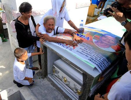Elvira Miranda, mother of Leover Miranda, a drug-related killings victim, cries in front of the tomb during a funeral march at the north cemetery in metro Manila