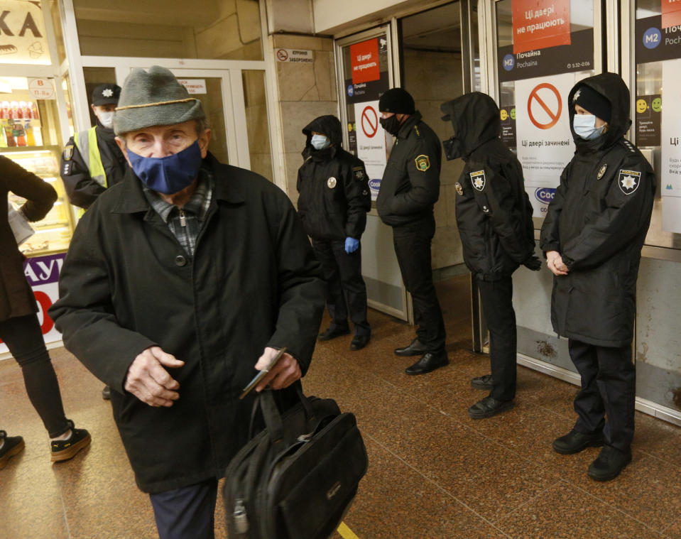 Policeman does not allow a man to enter a subway station because he has no passenger pass in Kyiv Ukraine, Monday, April 5, 2021. The city authorities have tightened an anti-coronavirus lockdown on Monday with more cases registered and hospitals overcrowded. (AP Photo/Efrem Lukatsky)