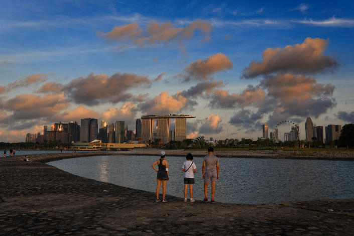 People look at the city skyline at sunrise on June 4, 2021 in Singapore. Singapore enters a month long heightened alert from May 16 to June 13 to curb the spread of COVID-19 cases in the local community. New restrictions on movements and activities have been introduced such as limiting social interaction to two, prohibiting dining out and a reduced operating capacity at shopping malls, offices and attractions. (Photo by Suhaimi Abdullah/NurPhoto via Getty Images)