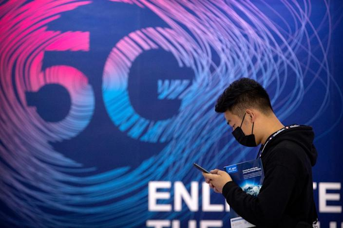 A person looks at a smartphone while walking past a sign advertising 5G services.