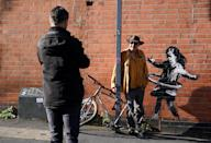 Nottingham residents take their photograph next to graffiti artwork, now confirmed to be the work of street artist Banksy, on a side of a property at Rothesay AVenue and Ilkeston Road, Nottingham. The artwork depicts a young girl playing with a tyre and is painted on a wall near to an abandoned bicycle that is missing a wheel.
