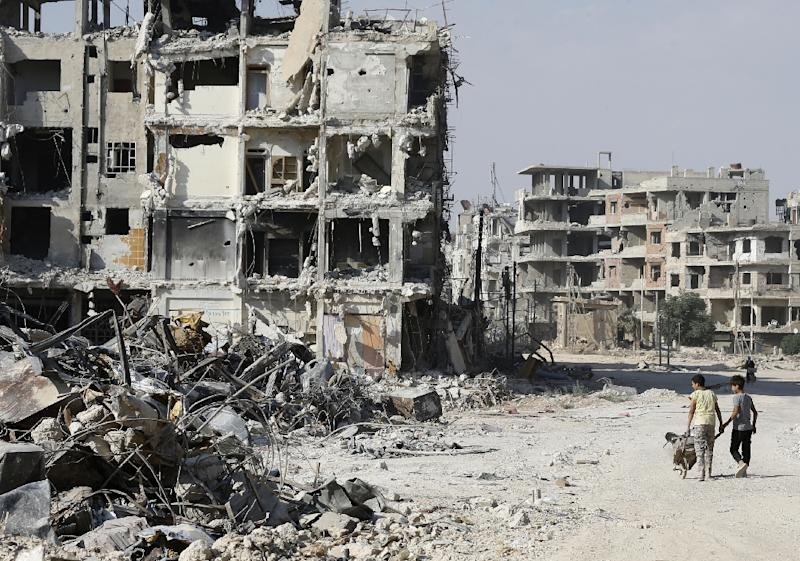 Syrian children walk by the rubble of destroyed buildings in Harasta, on the outskirt of the capital Damascus on July 15, 2018