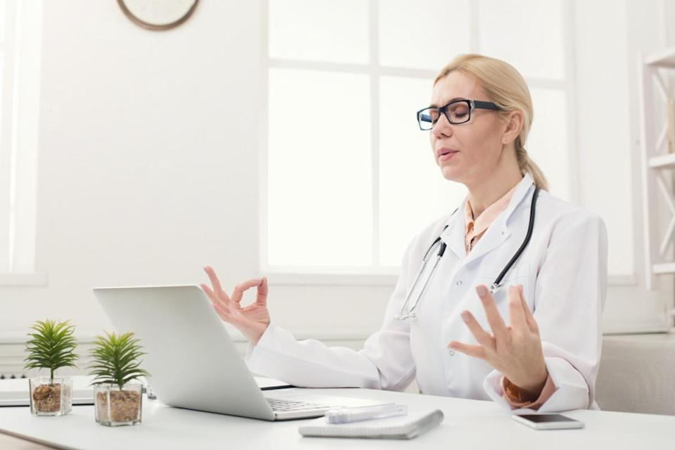 Female doctor meditating at her office