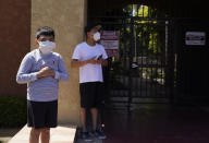 Francisco, 9, stands outdoors with his father Francisco Navas, as Los Angeles Police investigate the scene of a crime across their apartment complex in Reseda, Calif., Saturday, April 10, 2021. A woman discovered her three grandchildren, all under the age of 5, slain inside a Los Angeles apartment Saturday morning and their mother gone, police said. The mother of three children — all under the age of 5 — found slain inside a Los Angeles apartment Saturday morning has been arrested, police said. (AP Photo/Damian Dovarganes)