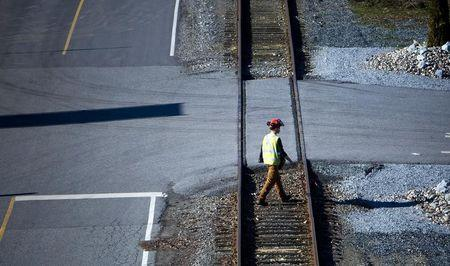 A railyard worker walks along the tracks at the Canadian Pacific railyard in Port Coquitlam
