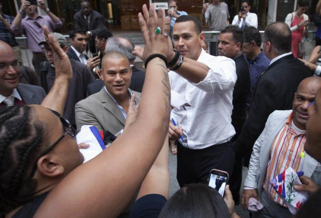 New York Yankees baseball player Alex Rodriguez high fives a supporter after leaving Major League Baseball's headquarters in New York