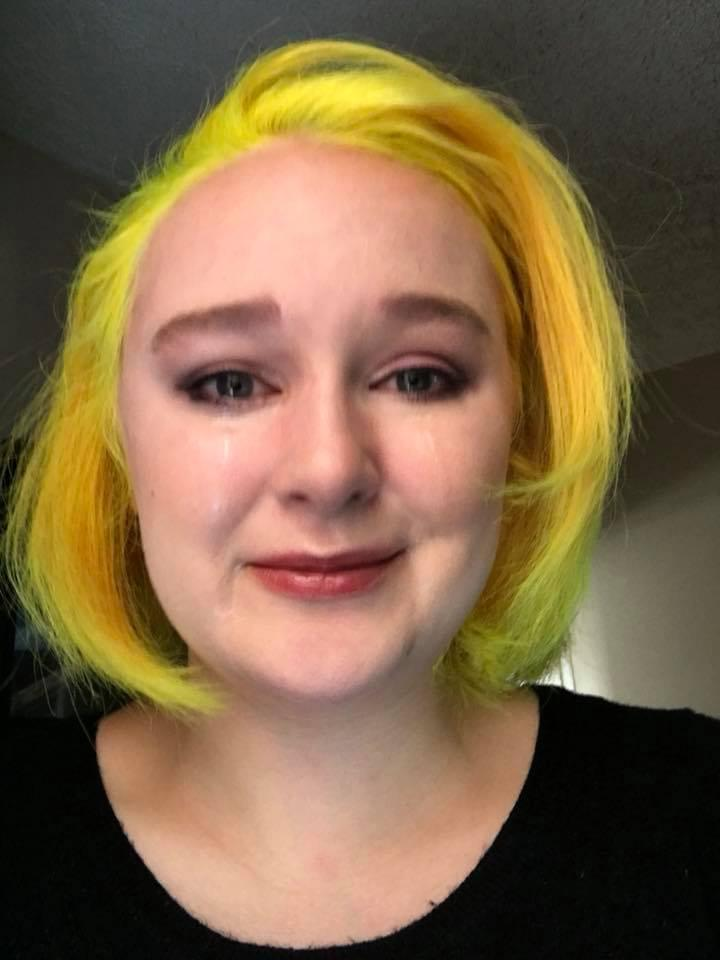 woman with yellow hair crying but trying to smile