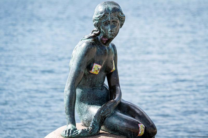 The statue was daubed with stickers as well as graffiti (via REUTERS)