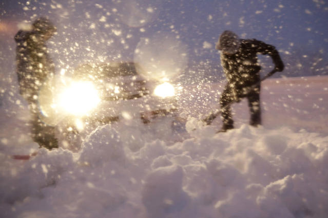 <p>Men shovel snow in attempt to free a vehicle stuck on a snowbank along Route 23 during a snowstorm, March 7, 2018, in Wayne, N.J. (Photo: Julio Cortez/AP) </p>