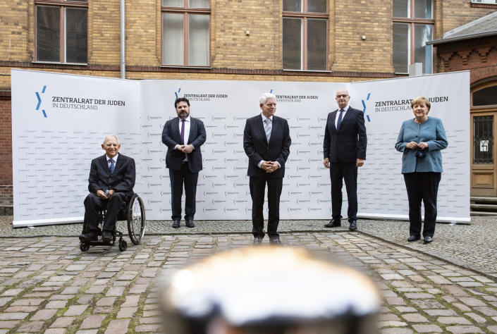 German Chancellor Angela Merkel, right, and Josef Schuster, center, President of the Central Council of Jews in Germany, joined Bundestag President Wolfgang Schaeuble, left, Gideon Joffe, second left, Chairman of the Jewish Community of Berlin, and Dietmar Woidke, second right, Minister President of Brandenburg and current President of the Bundesrat, in the courtyard of the New Synagogue for a group photo at the ceremony marking the 70th anniversary of the Central Council of Jews in Berlin, Germany, Tuesday, Sept. 15, 2020. The Central Council of Jews in Germany was founded on 19 July 1950 in Frankfurt am Main. (Bernd von Jutrczenka/Pool via AP)