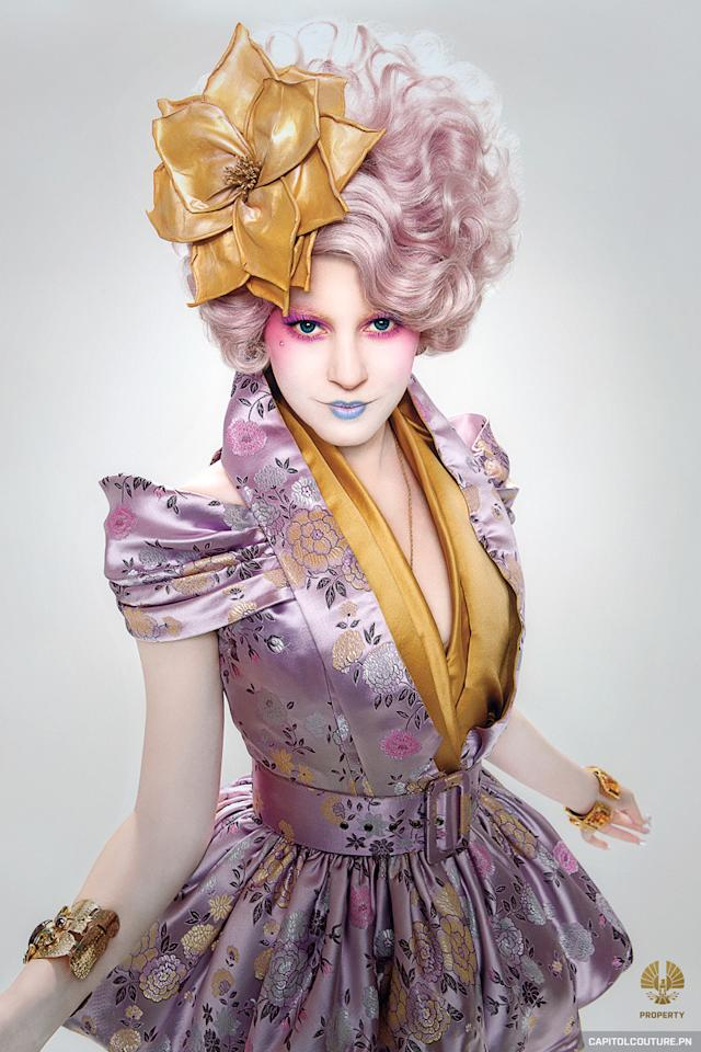 <p>Effie is next spotted on her home turf, at the Capitol of Panem, in a shiny, belted pink-and-gold get-up — her flower-adorned wig an even brighter shade of pink — as she tours Peeta (Josh Hutcherson) and Katniss around their swanky, temporary housing.</p>