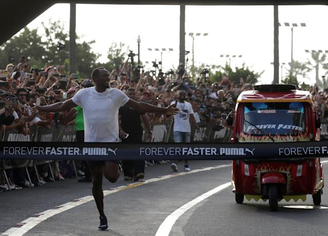 Usain Bolt runs against a moto-taxi as part of a sponsored event in Lima, Peru - April 2, 2019 REUTERS/Henry Romero