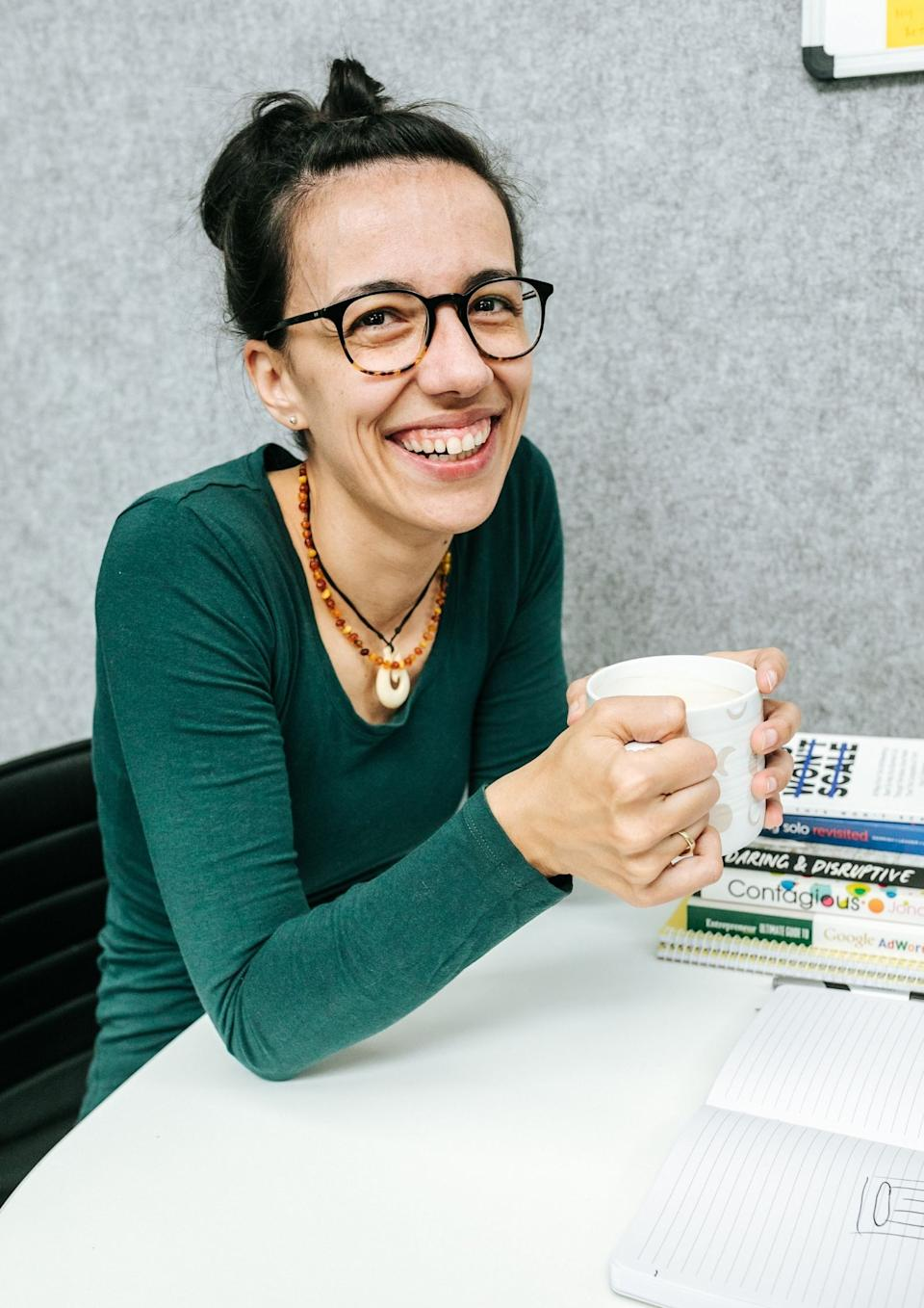 Pictured: Branka Injac Misic seated at office desk with mug in hand, smiling. Image: Supplied