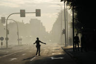 A police officer gestures in the area where a building went on fire in Milan, Italy, Sunday, Aug. 29, 2021. (AP Photo/Luca Bruno)