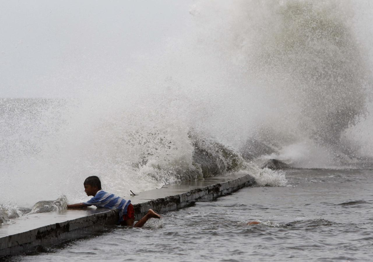 A boy holds on to the concrete bank as rough waves crash along the coast of Manila Bay brought by Super Typhoon Usagi in Navotas City, metro Manila September 21, 2013. The year's most powerful typhoon slammed into the Philippines' northernmost islands on Saturday, cutting communication and power lines, triggering landslides and inundating rice fields, officials said. Packing winds of 185 kph (114 mph) near the center and gusts of up to 220 kph, Typhoon Usagi weakened after hitting the Batanes island group, and is moving slowly west-northwest at 19 kph towards southern China, the weather bureau said. REUTERS/Romeo Ranoco (PHILIPPINES - Tags: DISASTER SOCIETY ENVIRONMENT TPX IMAGES OF THE DAY)