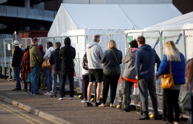 FILE PHOTO: People queue outside a test centre in Southend-on-sea