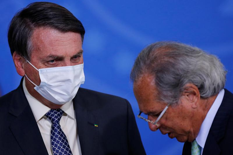 Brazil's President Jair Bolsonaro talks with Brazil's Economy Minister Paulo Guedes during a ceremony to launch a program to expand access to credit at the Planalto Palace in Brasilia, Brazil, August 19, 2020. REUTERS/Adriano Machado