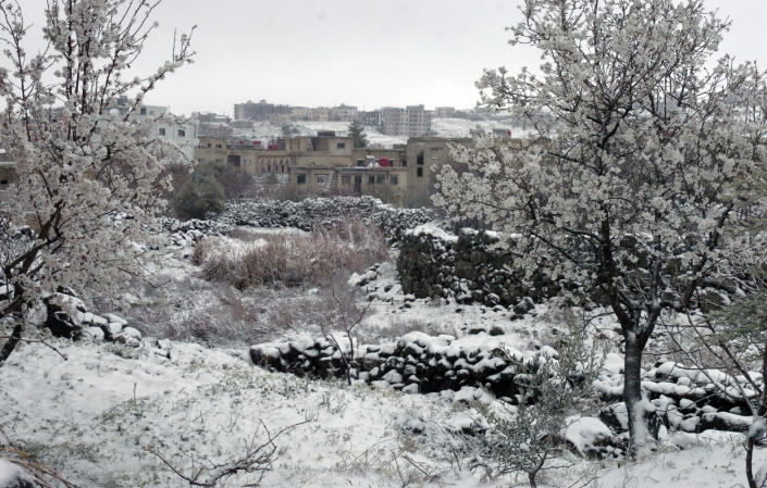 In this photo released by the Syrian official news agency SANA, snow covers a village in the southern province of Sweida, Syria. Wednesday, Feb. 17, 2021. Snow blanketed parts of Syria, Lebanon, Jordan and Israel on Wednesday, blocking roads, disrupting traffic and postponing vaccination campaigns against COVID-19 and even exams at some universities. (SANA via AP)