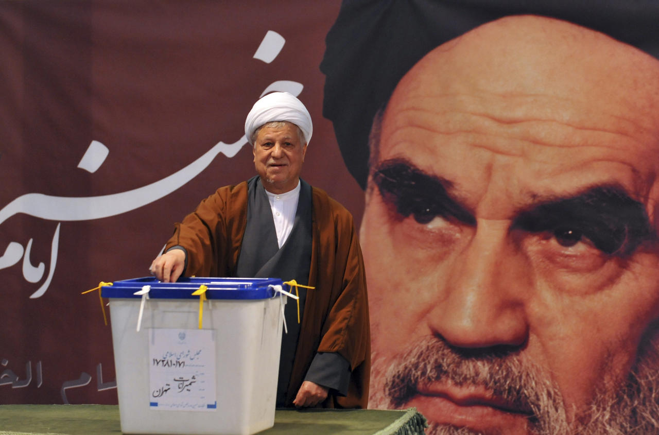 In front of a portrait of late Iranian leader Ayatollah Khomeini, former President Akbar Hashemi Rafsanjani casts his ballot for the parliamentary elections at a polling station in Tehran, Iran, Friday, March 2, 2012. The balloting for the 290-member parliament is the first major voting since the disputed re-election of President Mahmoud Ahmadinejad in June 2009 and the mass protests and crackdowns that followed. (AP Photo/ISNA, Ruhollah Vahdati)